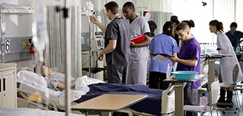 Health students working in a mock hospital room